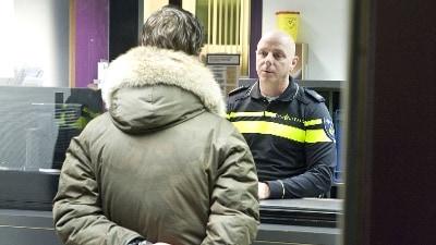 Arrestant voor de balie van politiebureau in gesprek met agent
