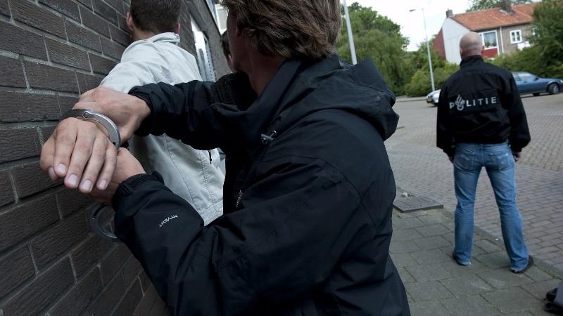 agent drukt verdachte tegen muur om boeien om te doen
