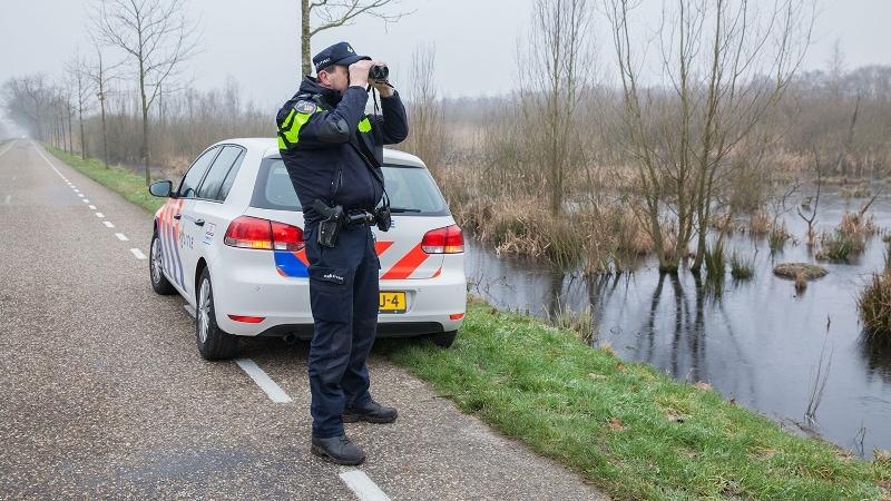 Agent met verrekijker inspecteert natuurgebied