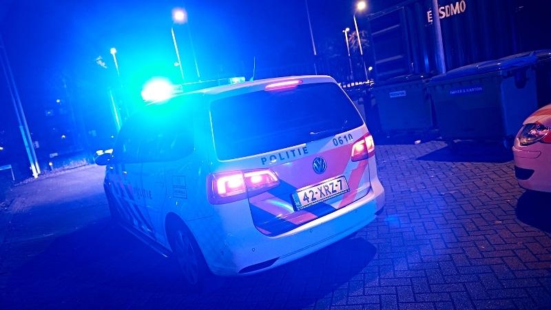 Wegrijdende politieauto met zwaailicht in nacht
